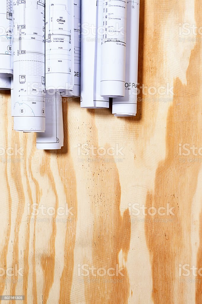 Rolled-up blueprints with copy space beneath wooden background royalty-free stock photo