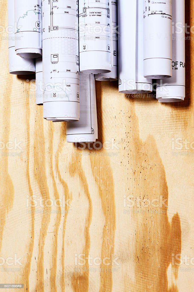 Rolled-up building plans over wooden surface with copy space royalty-free stock photo