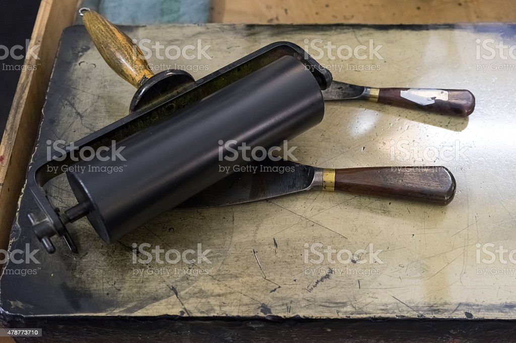 Roller and spatula on table in the printing stock photo
