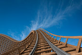 Wooden roller coaster track with blue sky in the background.