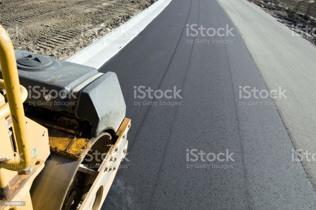 Roller Compactor on Fresh Asphalt Road stock photo