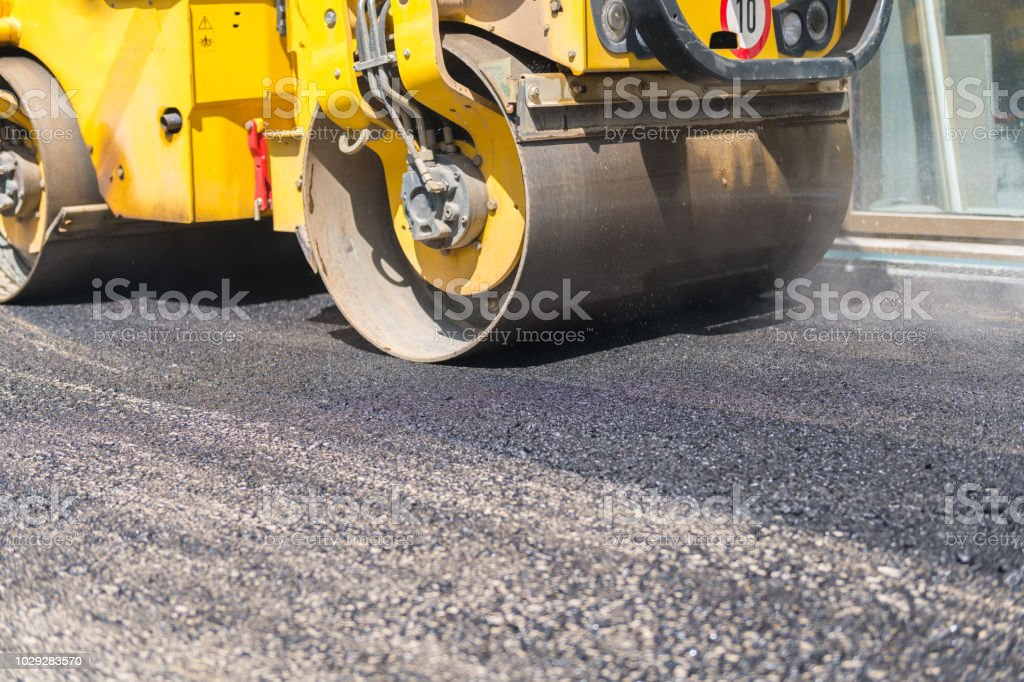 Roller drives over fresh asphalt and rolls the surface flat.