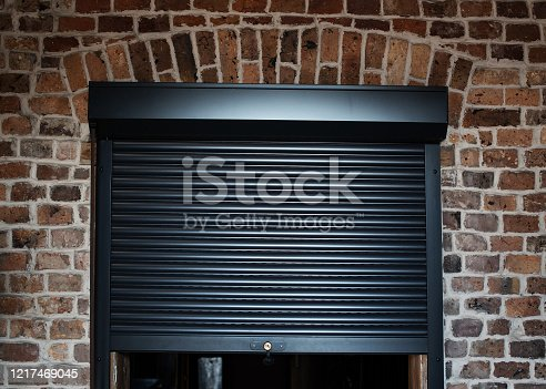 Black roller shutter and red brick wall