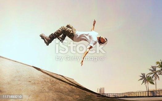 Rollerskater man is performing tricks in skatepark on sunset.
