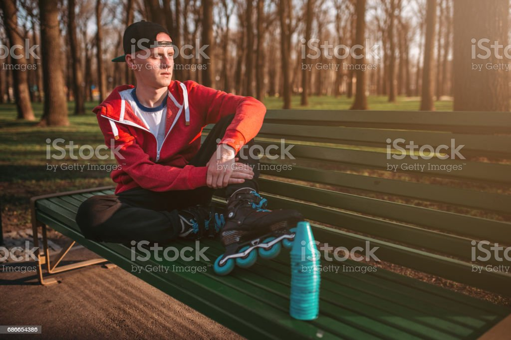 Roller skater posing on the bench in skates royalty-free stock photo