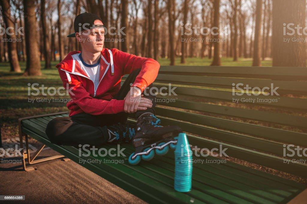 Roller skater posing on the bench in skates royalty-free stock photo