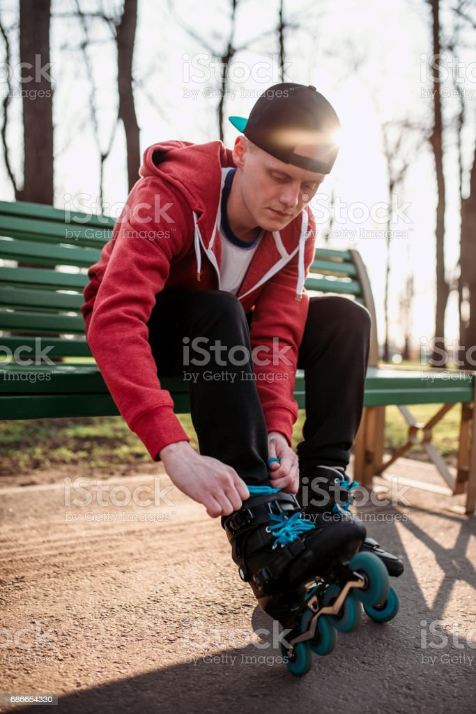 Roller skater sitting on bench and lace up skates royalty-free stock photo