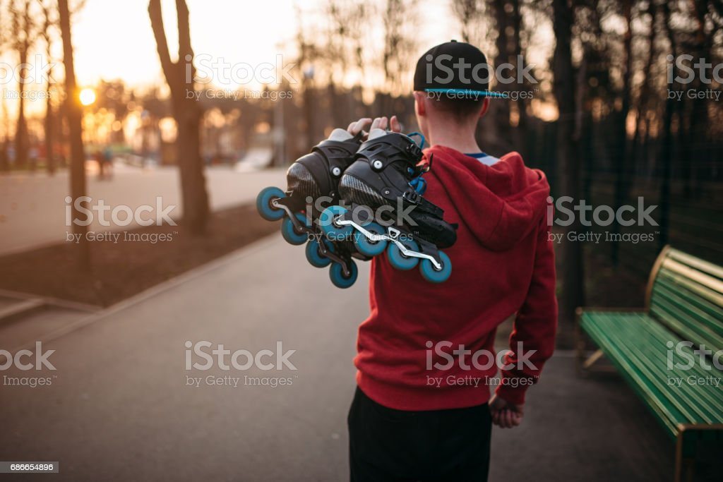 Roller skater with skates in hands, back view royalty-free stock photo