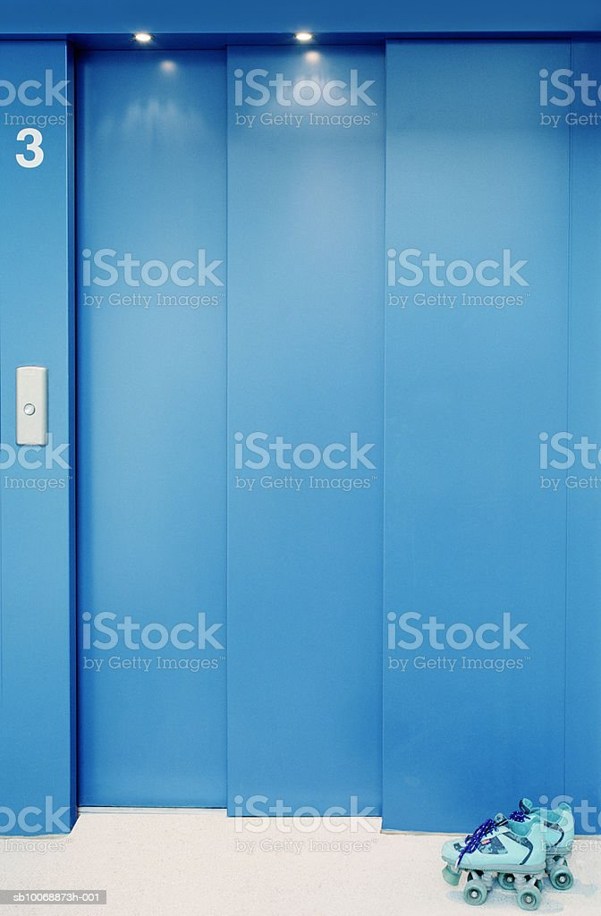 Roller skates in front of elevator royalty free stockfoto