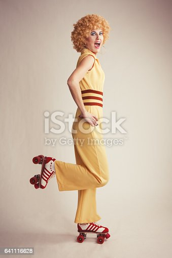 A woman in a 70's jumpsuit roller skating.