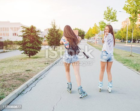 Two young women are roller skating down the sidewalk