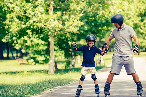 roller skating grandfather and grandson - indumento sportivo protettivo foto e immagini stock