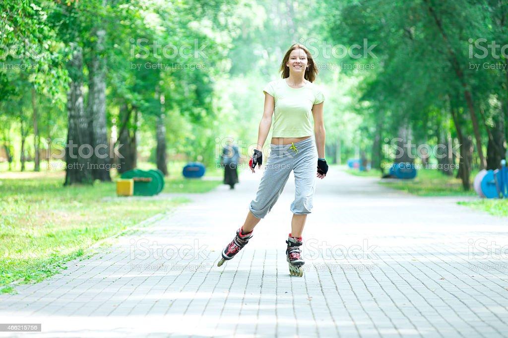 Roller skating sporty girl in park rollerblading on inline skate stock photo