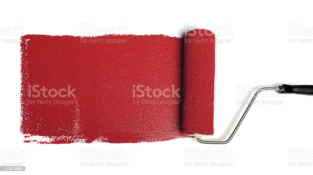 Roller with red paint on a white wall stock photo