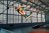 Extreme sport competition show. Rollerblader jump high from big air ramp performing trick. Indoors skate park equipment. Aggressive roller blading contest.