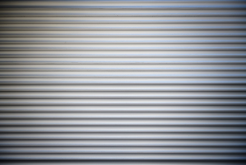 High resolution photograph of a metal rolling garage door with vignette.