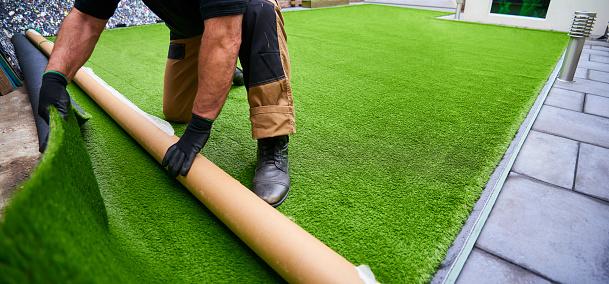 Installing artificial grass in modern garden of home