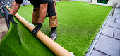 Installing artificial grass in modern garden of home