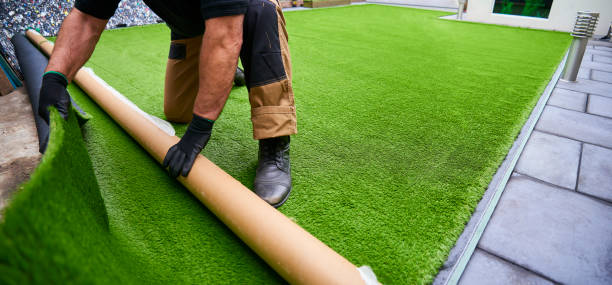 Rolling artificial grass out to fit Installing artificial grass in modern garden of home turf stock pictures, royalty-free photos & images