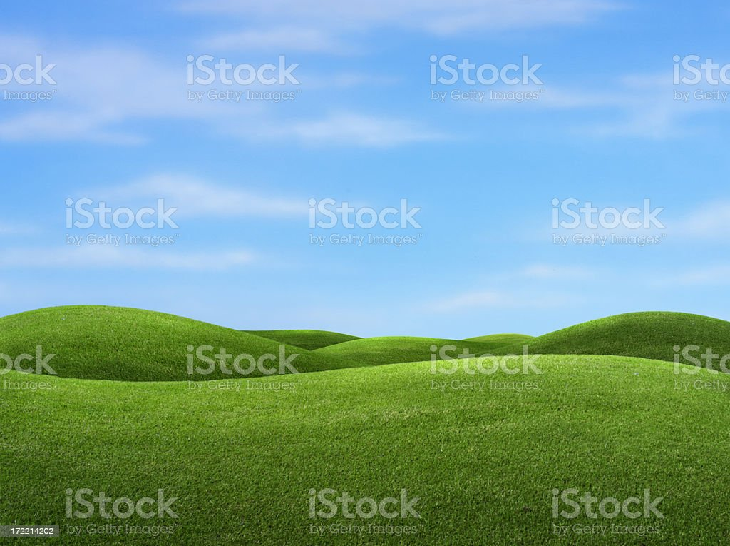 Rolling green hills with blue sky in background stock photo