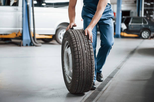 Rolling on the floor. Employee in the blue colored uniform works in the automobile salon stock photo