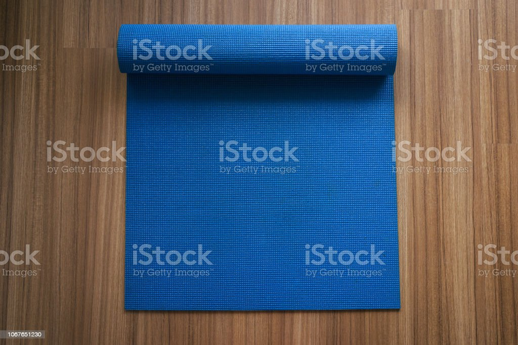 Rolling or folding blue yoga mat after a workout,Exercise equipment'nHealthy fitness and sport concept,Top view and copy space stock photo