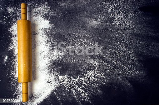 istock Rolling pin and white flour on a dark background. Free space for text . 925750588