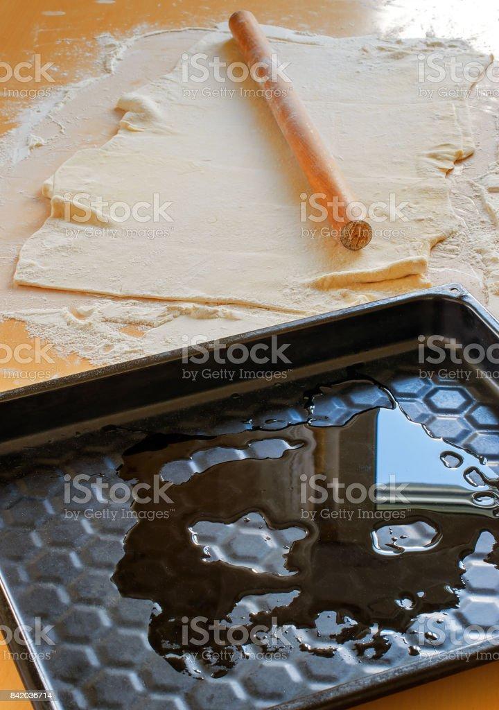 Rolling pin, dough and baking sheet stock photo