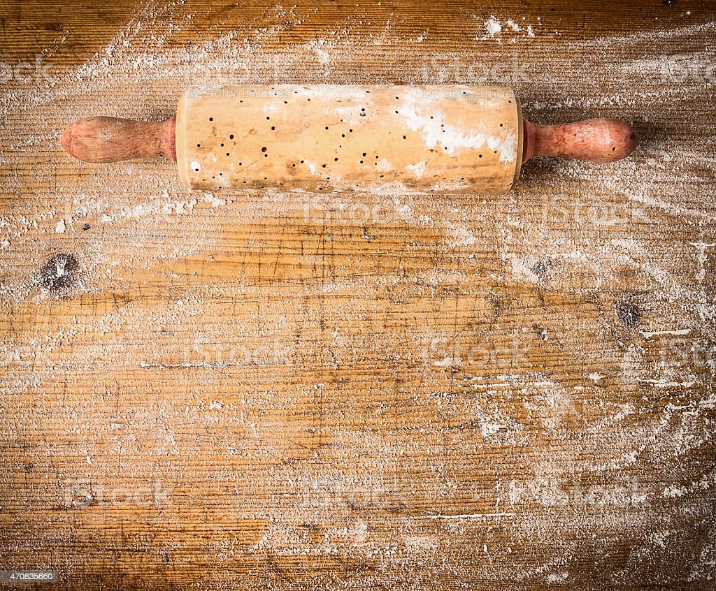 Rolling pin on old wooden background with  wheat flour stock photo