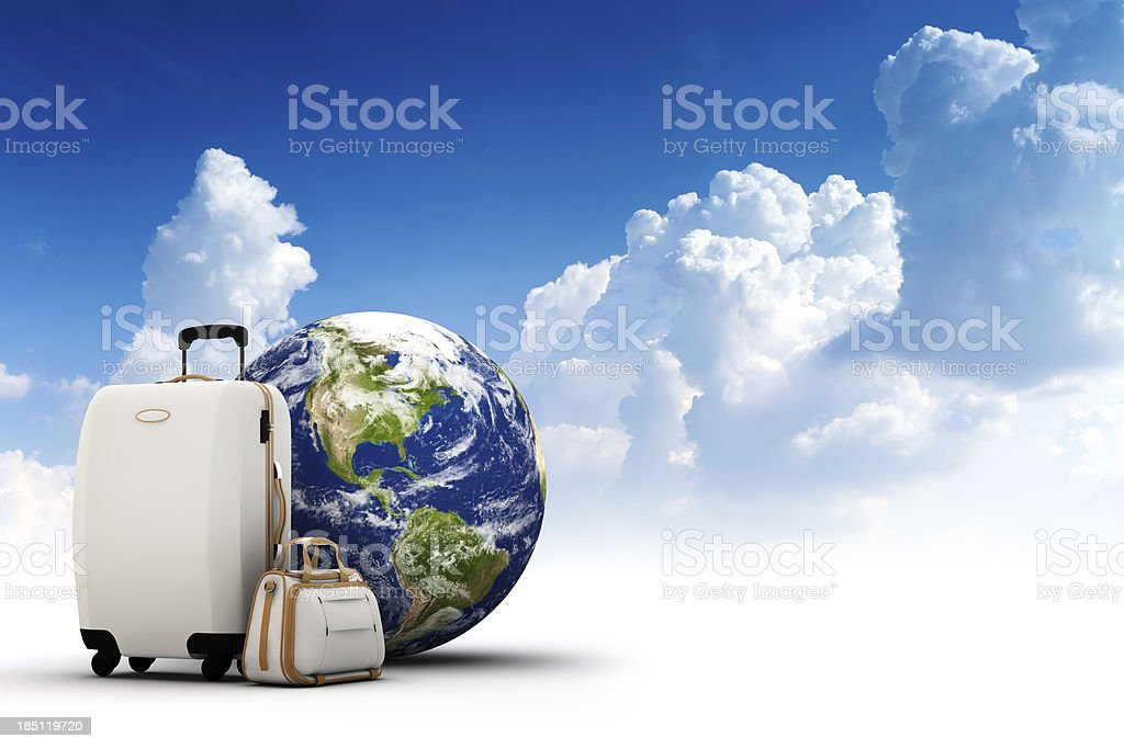 Rolling suitcase, bag and Earth with beautiful sky on background stock photo