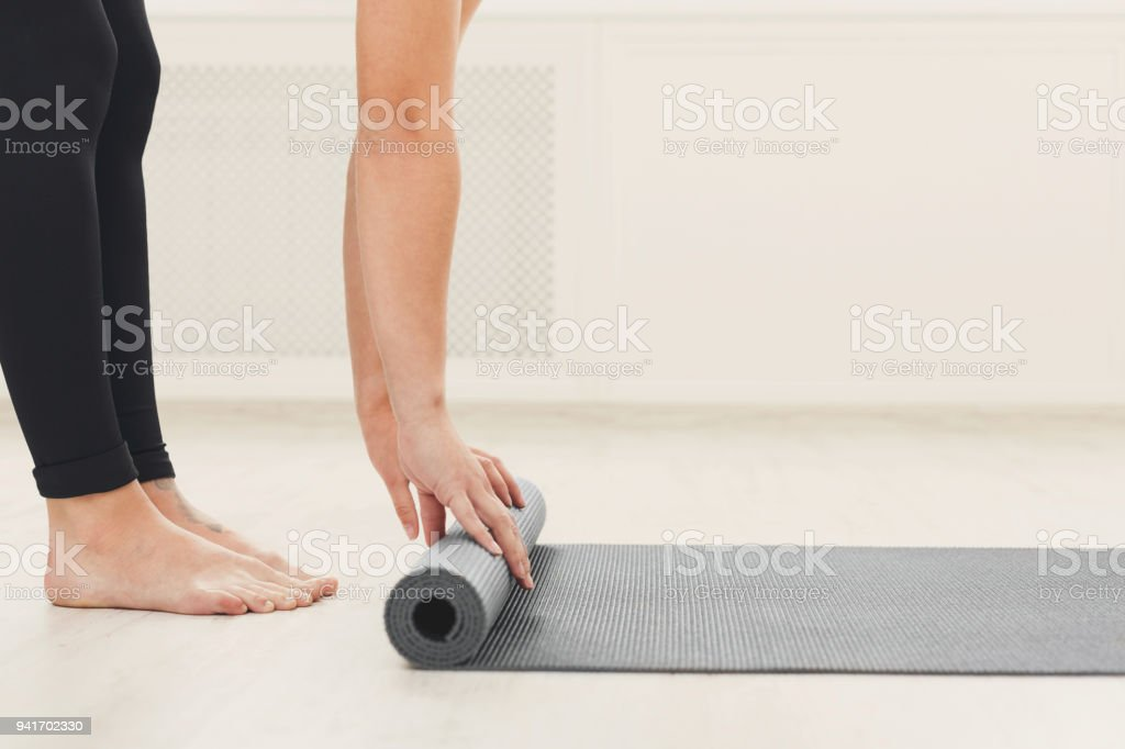 Rolling up fitness mat for exercise copy space stock photo