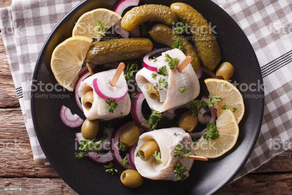 rollmops herring with olives, onions and pickles close up. Horizontal top view stock photo