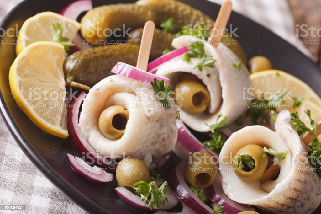 rollmops herring with olives, onions and pickles close up. horizontal stock photo