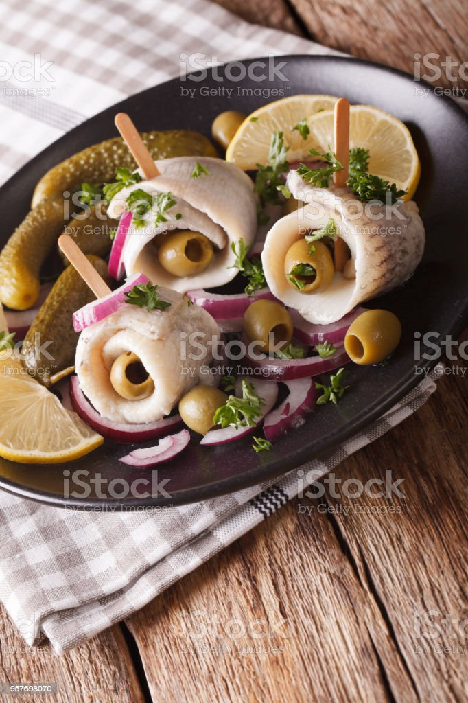 rollmops herring with olives, onions and pickles close up. Vertical stock photo