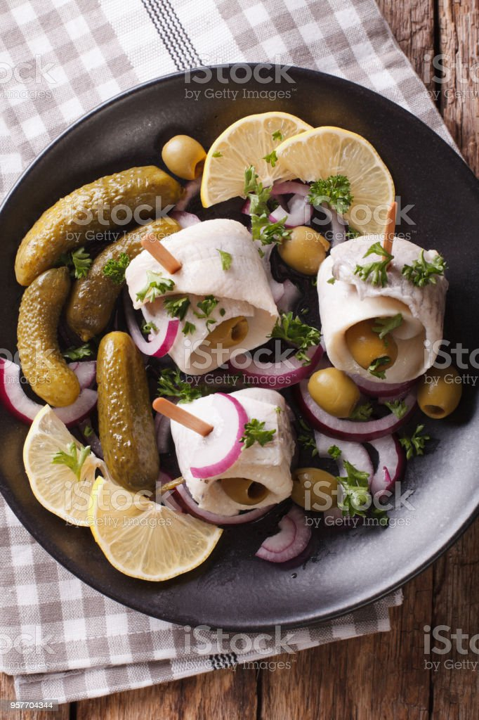 rollmops herring with olives, onions and pickles close up. Vertical top view stock photo