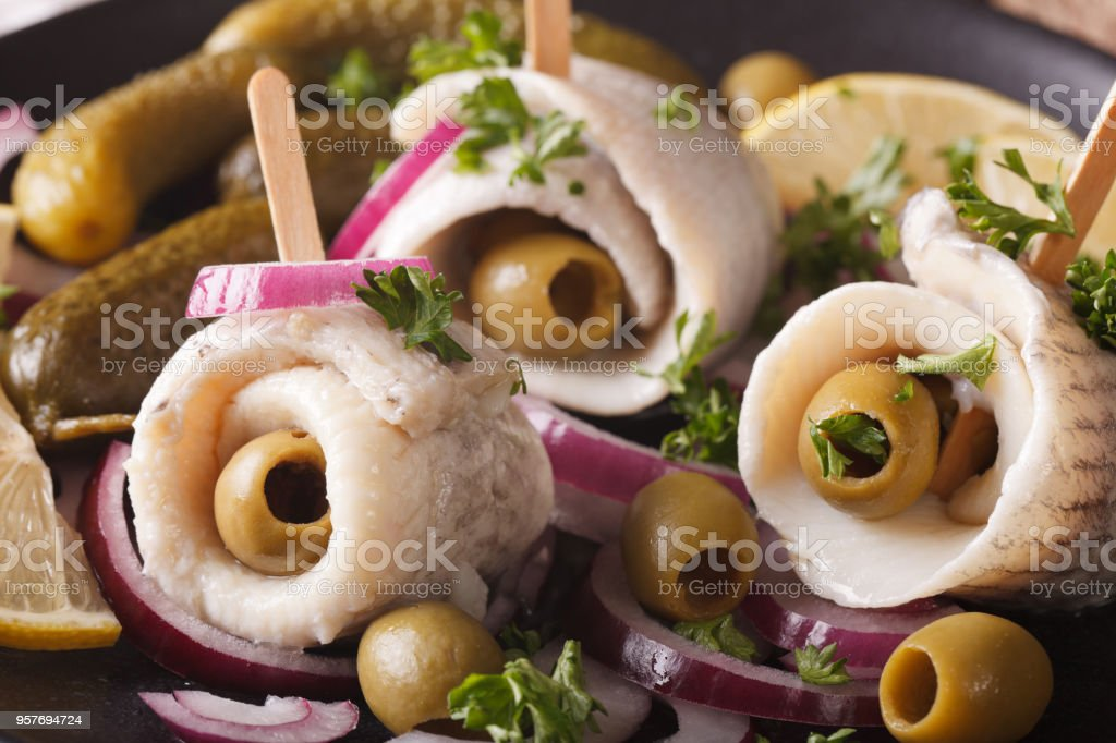rollmops herring with olives, onions and pickles macro. horizontal stock photo