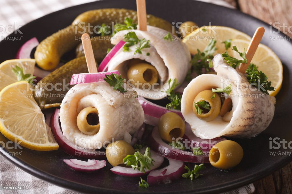 rollmops herring with olives, onions, pickles and lemon close-up. horizontal stock photo