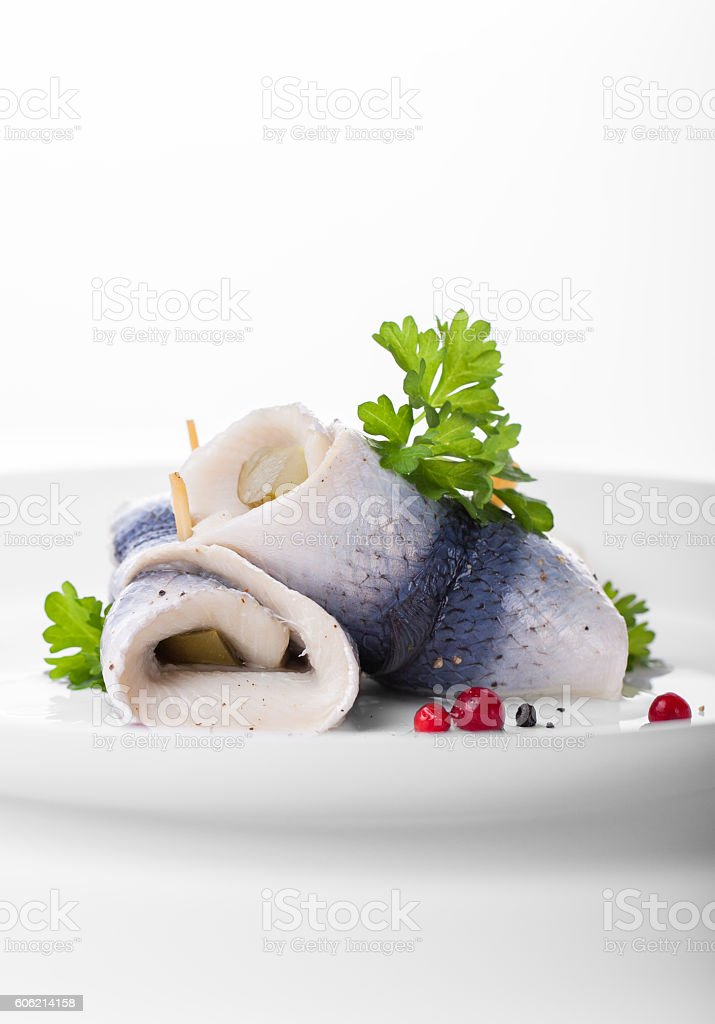 Rollmops (rolled marinated herring) with marinated cucumber, salt, pepper stock photo