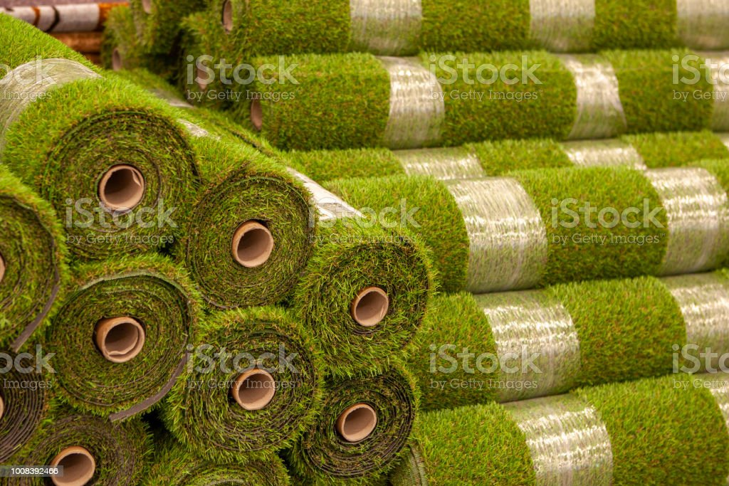 Rolls artificial grass in store of building materials. Cover for...