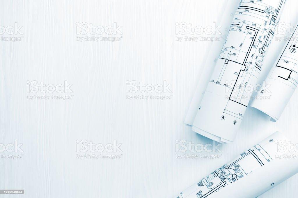 rollos de planos arquitectónicos y planos en el espacio de trabajo de arquitecto foto de stock libre de derechos