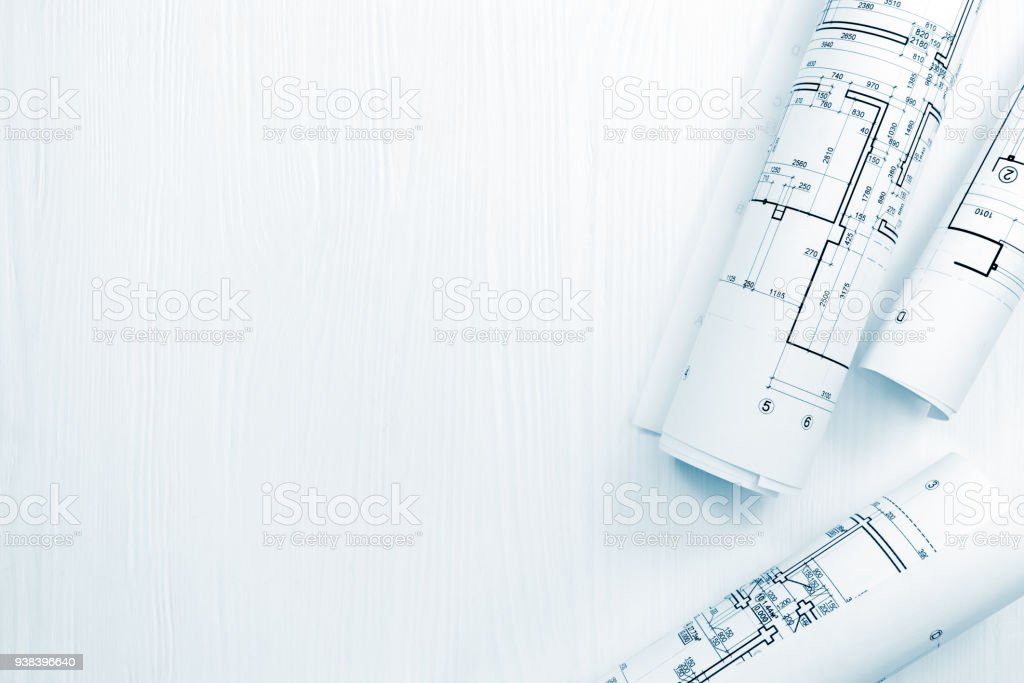 rolls of architectural plans and blueprints on architect workspace stock photo