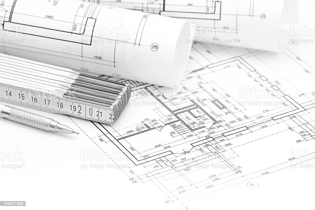 rolls of blueprints, folding rule and pencil on floor plan stock photo