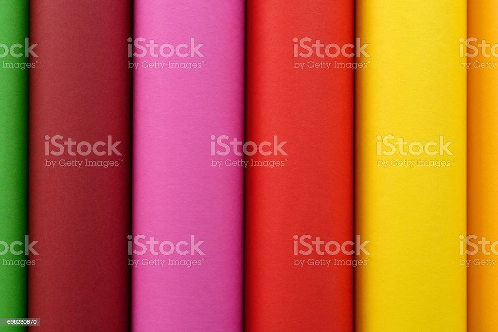 Rolls of colored paper in green, brown, pink, red yellow and orange stock photo