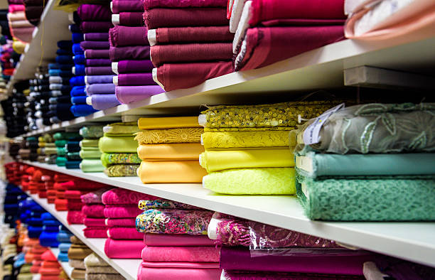 rolls of fabric and textiles in a factory shop store - textile stock photos and pictures