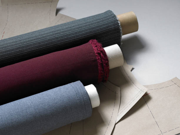 Rolls of fabric ion top of designs sheets stock photo