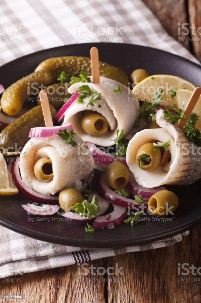 rolls of herring with olives, onions, pickles and lemon close-up. vertical stock photo