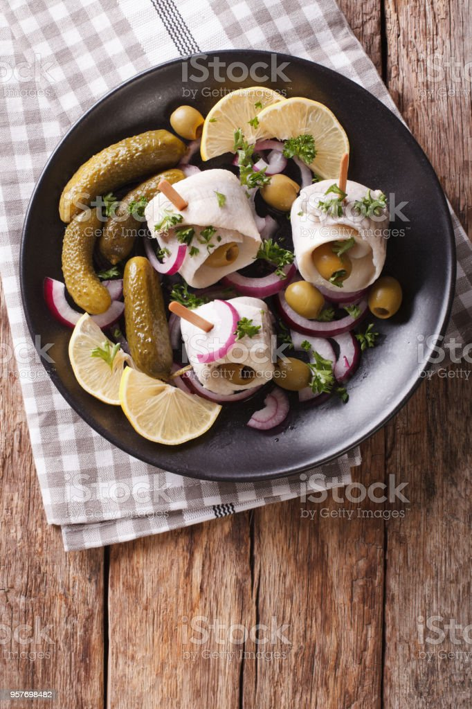 rolls of marinated herring with olives, onions, pickles and lemon close-up on a plate. Vertical top view stock photo