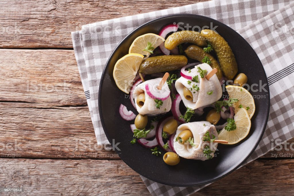 rolls of marinated herring with olives, onions, pickles and lemon close-up on a plate. horizontal top view stock photo