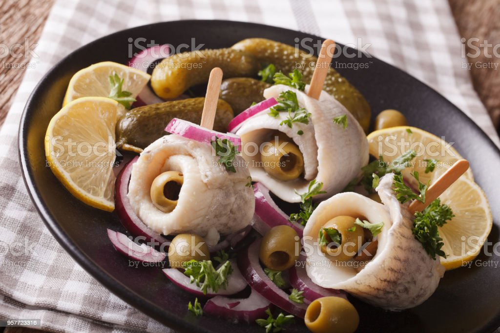 rolls of marinated herring with olives, onions, pickles and lemon close-up on a plate. Horizontal stock photo