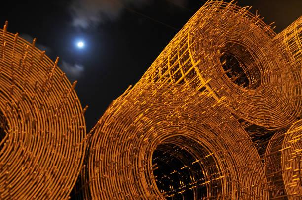 Rolls of Stacked Reinforcement Steel in the Moonlight stock photo